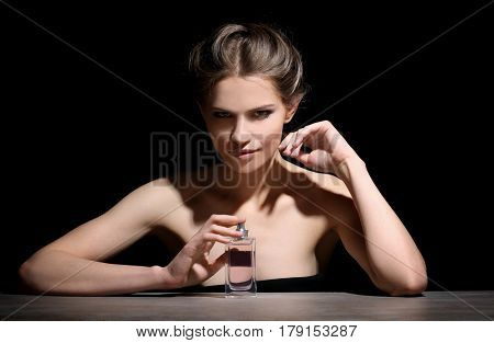 Beautiful young woman with bottle of perfume on dark background