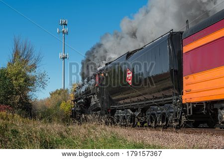 CHANHASSEN MN - OCTOBER 9 2016: The Milwaukee Road #261 steam train travels by cell tower on trip from Minneapolis to Winthrop MN. This line has not had regular passenger trains traffic since 1960.