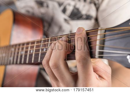 A picture of an acoustic guitar classical color in the hands of a guitarist with a clamped chord. In the frame only the left hand