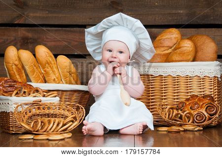 Child cooks a croissant in the background of baskets with rolls and bread