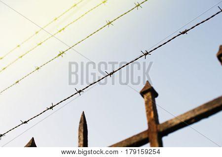 Prison fence in barbed wire fence closeup - security escape concept - sun flare on a corner
