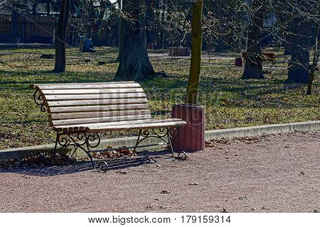 A brown bench in the park and an urn
