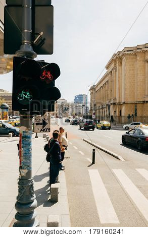BUCHAREST ROMANIA - APR 1 2016: Vertical image of pedestrians waiting to cross the Calea Victoriei Boulevard avenue with the The National Museum of Art of Romania in the background