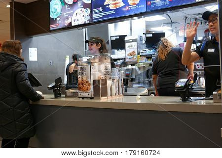 Coquitlam, BC, Canada - February 28, 2017 : Motion of worker waving for next on line customer at mcdonalds check out counter inside Coquitlam shopping mall