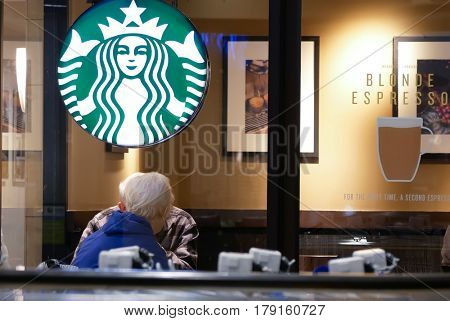 New Westminster, BC, Canada - March 03, 2017 : One side of people drinking coffee and chatting inside Starbucks store