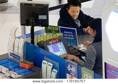 Burnaby, BC, Canada - March 07, 2017 : Top shot of people buying lottery ticket inside mall lottery ticket retailer