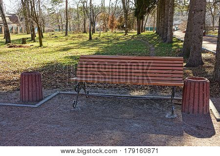 Urn and wooden bench in the park on the road near the curb