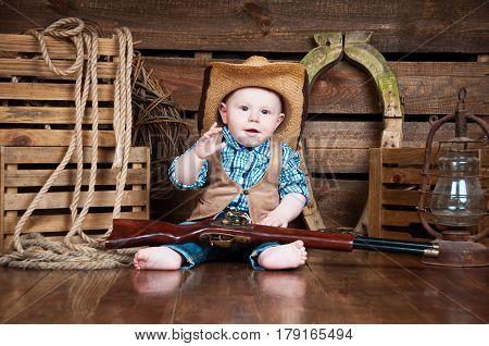 Portrait of a small boy in cowboy decor.