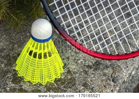Neon green shuttlecock and red badminton racket leaning on stone wall closeup recreational activity background