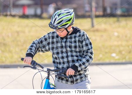 Preteen boy walking bicycle looking at handlebars getting ready to ride healthy activity concept