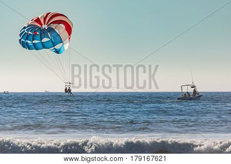 San Diego, USA - November 1, 2015: Couple of women parasailing in San Diego California with blue and red parachute
