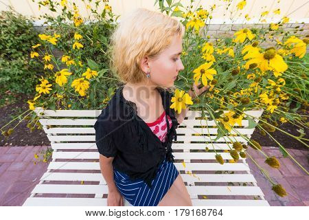 Closeup of young woman smelling tall sunflower yellow daisy flowers on bench