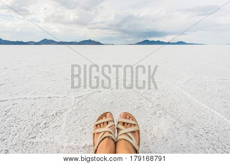 White Bonneville Salt Flats landscape with womans feet and sandals