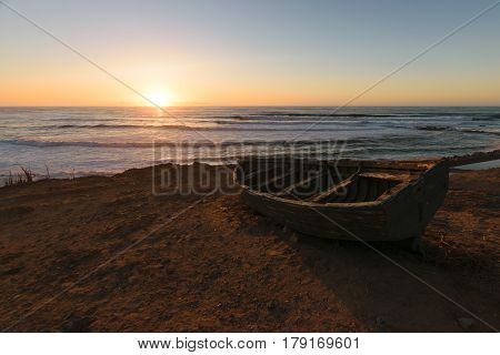 Beautiful image of an old fisherman boat at the coast of the Atlantic Ocean at sunset in Morocco.