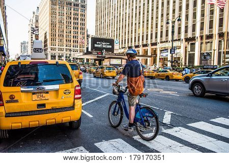 New York City, USA - June 18, 2016: Man on a bicycle crossing road filled with taxi cabs in Madison Square Garden