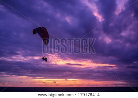 Paramotor glider flying in the sky over beautiful colorful clouds at sunset Bali Indoensia