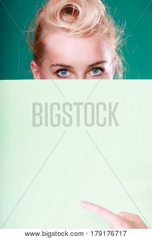Woman standing behind white board at eye level half face only pointing at blank space. Studio shot on blue green background