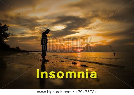Creative conceptual,Insomnia,word on photo with man alone on the beach during sunset.Calm sea with rippling waves.