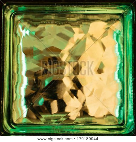 Green square glass block close up. Building material. Element of the wall. Refraction of light inside a glass object creates an interesting effect.