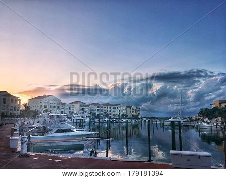 Boats on the water in a vacation spot with the sun setting over the water