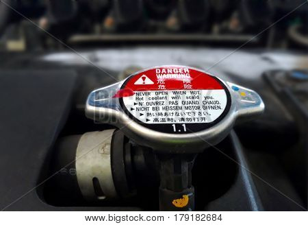 Car radiator cap with warning sign in close up