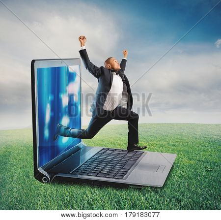 Businessman leaves the screen of a computer to a lawn. Technology addiction concept