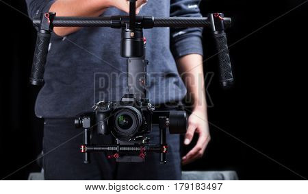Photographer using hand held camera stablizer equipment