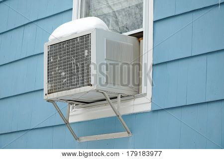 old air conditioner installed on house window after winter snow