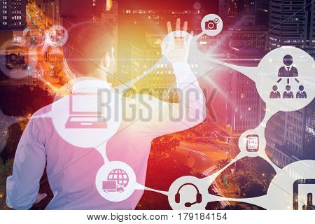 Rear view of businessman pretending to touch invisible screen against illuminated roads by buildings in city 3d