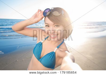 beauty woman wear bikini and selfie happily with sea