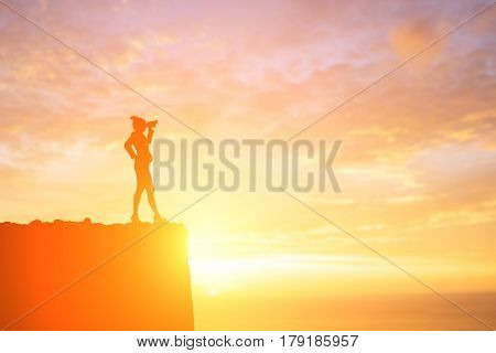 silhouette of business woman take binocular telescope with sunset