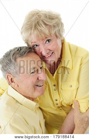 A loving senior couple happily snuggling together. On a white background.