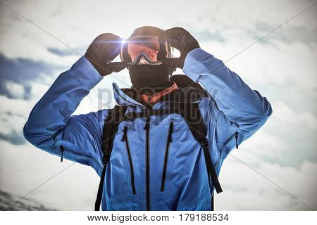 White background with vignette against skier adjusting his sunglasses