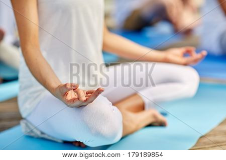 fitness, sport, yoga, people and healthy lifestyle concept - close up of woman meditating in easy sitting pose