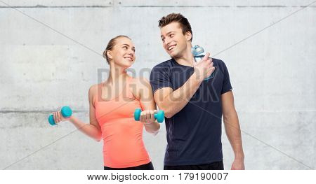 sport, fitness and people concept - happy sportive man and woman with dumbbell and water bottle over concrete wall background