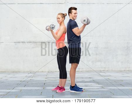 sport, fitness and people concept - happy sportive man and woman with dumbbells flexing muscles over concrete wall background