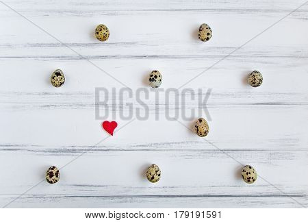 Decorative light pattern with quail eggs and a heart on white wooden vintage table. Flat lay top view natural still life eggs polka dot
