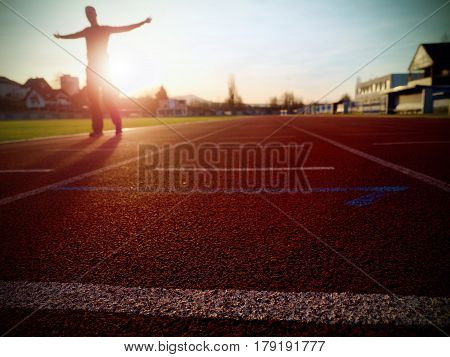Tall Man Running On Red Running Racetrack On The Stadium.