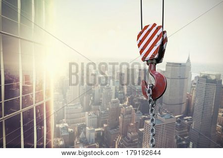 Studio Shoot of a crane lifting hook against image of a city landscape on a sunny day