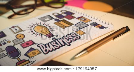 Digital generated image of business text with various icons against high angle view of notepad and pen on desk