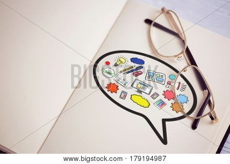 Composite image of computer icons in speech bubble against metallic eyeglasses on wooden table