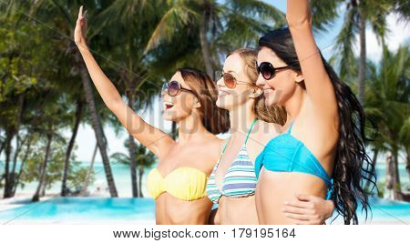 summer holidays, travel, people and vacation concept - happy young women in bikinis and shades hugging and waving hands over exotic tropical beach with palm trees and pool background