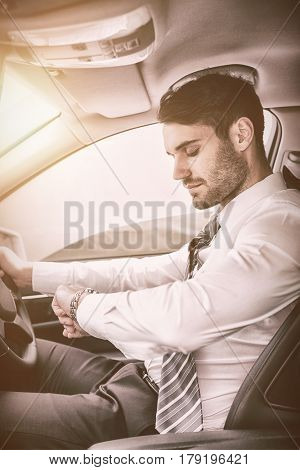Young businessman checking time while sitting on drivers seat in his car