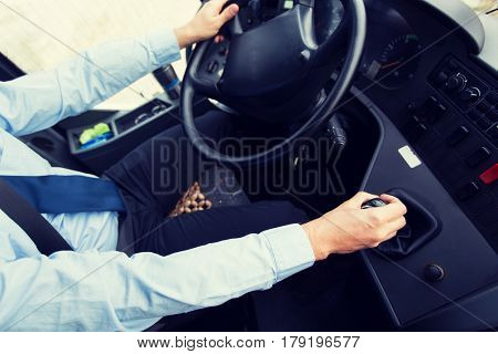 transport, transportation, tourism, road trip and people concept - close up of bus driver steering wheel and driving passenger bus