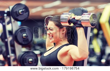 sport, fitness, bodybuilding, weightlifting and people concept - young woman with dumbbell flexing muscles in gym from back poster