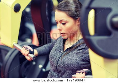fitness, sport, bodybuilding, exercising and people concept - close up of young woman flexing muscles on seated chest press machine in gym