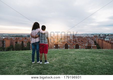 Siblings embraced looking at Madrid cityscape at dusk from a residential district with sunlight at background