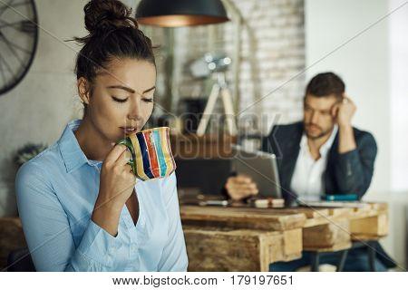Young businesswoman drinking tea, having break.