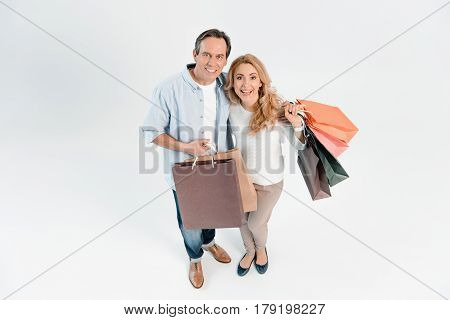 Happy Middle Aged Couple Holding Shopping Bags And Smiling At Camera