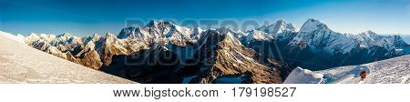 Great Sunny Panorama of Roof of the World Everest and other highest Peaks in day sunlight and brave Mountain Climbers walking on Glacier